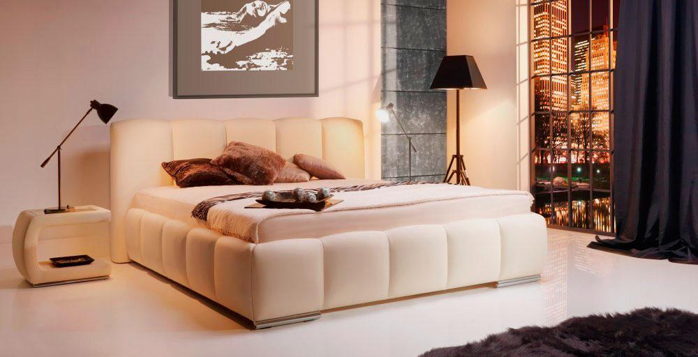 Мягкая белая кровать в интерьере спальной комнаты