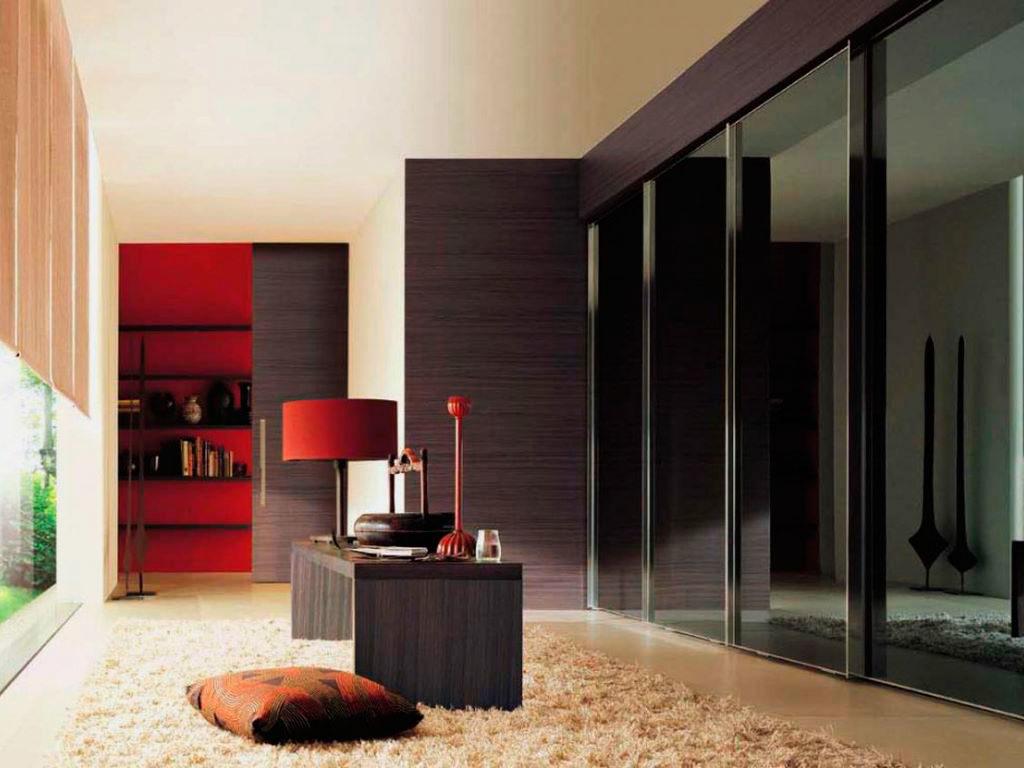 Интерьере комнаты с большим встроенным шкафом до потолка с черным стеклянным фасадом