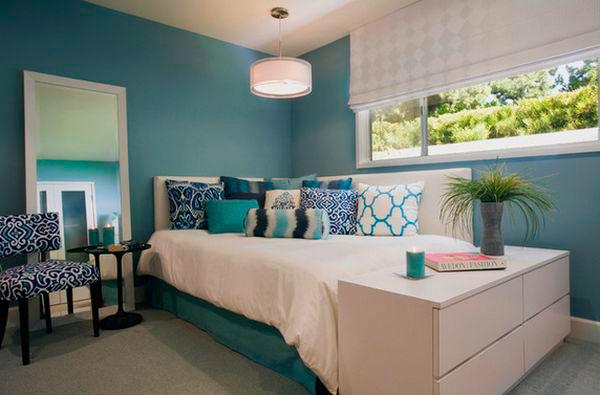 Интерьер спальной с угловой кроватью у окна