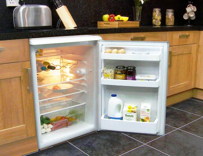 Фото маленького холодильника встроенного в нижнюю кухонную тумбу