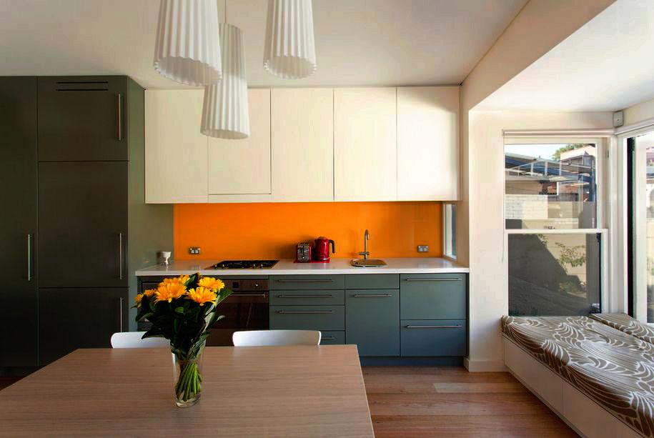 Фото линейной кухни с навесными шкафами до потолка и пеналами под встраиваемую технику