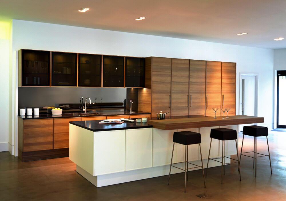 Двулинейный кухонный гарнитур с островом и стеклянными тонированными фасадами верхнего ряда шкафов