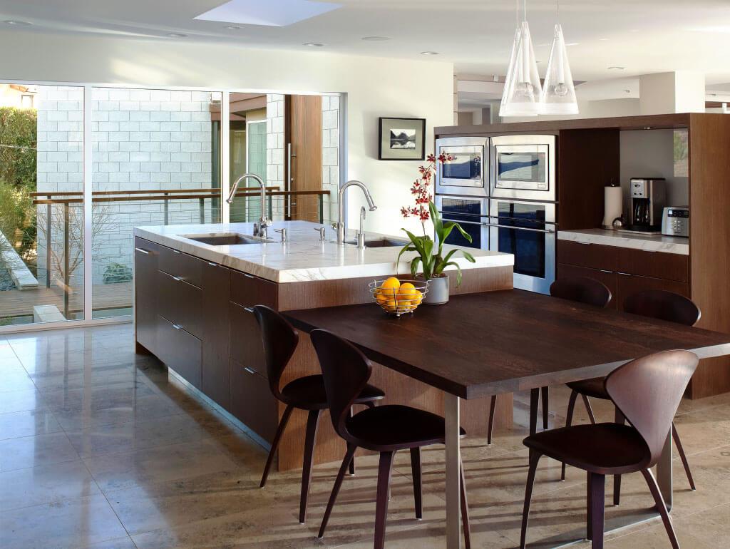 Интерьер кухни с кухонным островом совмещенным со столом