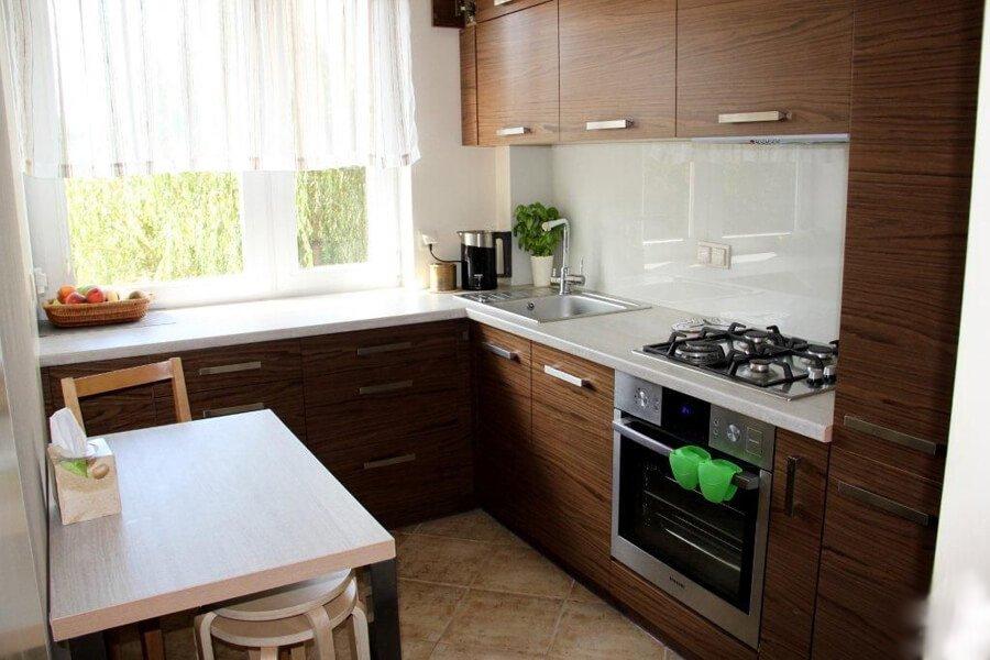 Угловой гарнитур на маленькой кухне у окна
