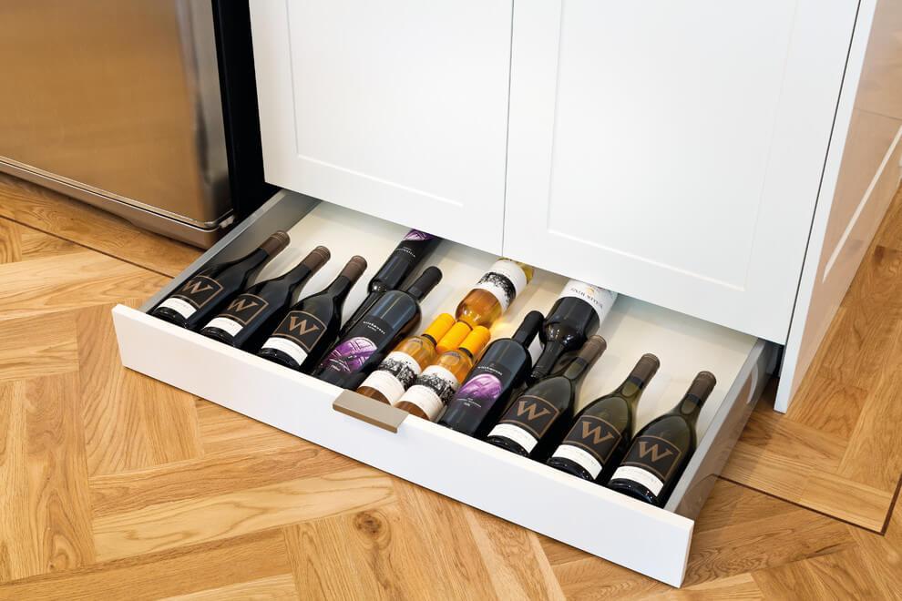 Выдвижной ящик с бутылками установленный в цоколь тумбы