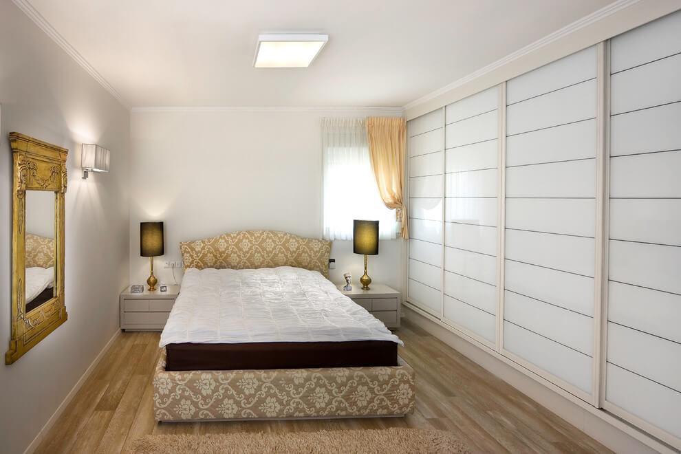 Встроенный шкаф-купе во всю стену в спальной комнате