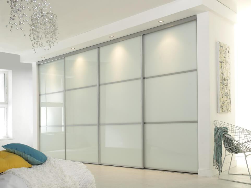 Встроенный шкаф купе в спальной со стеклянными глянцевыми фасадами