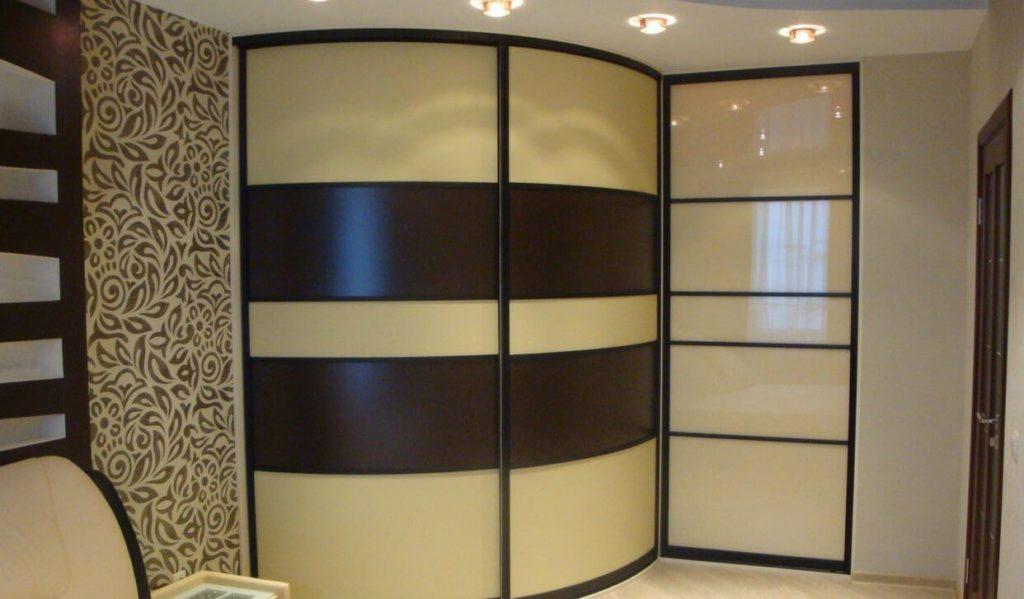 Радиусный встроенный шкаф в спальной с подсветкой в потолке