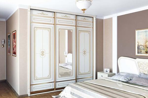 Встроенный в нишу шкаф в спальной с фасадами в классическом стиле