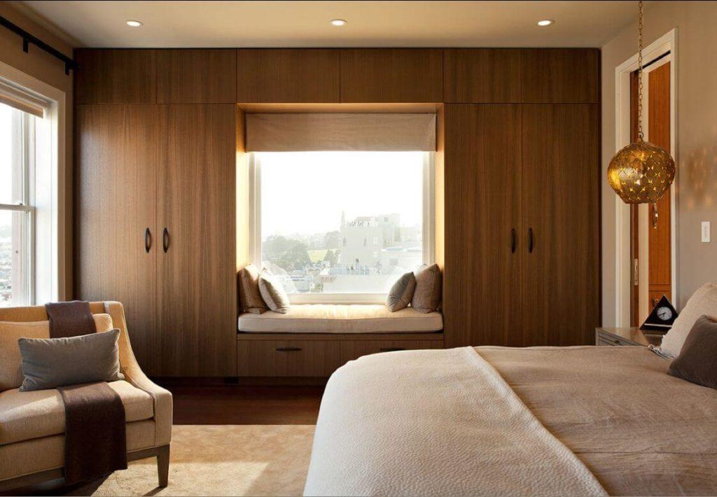 Встроенный шкаф во всю стену у окна в спальне