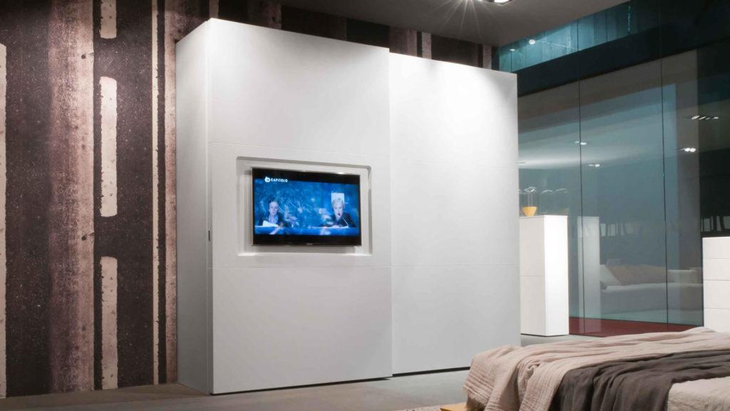 Шкаф купе с телевизором на фасаде в интерьере спальной