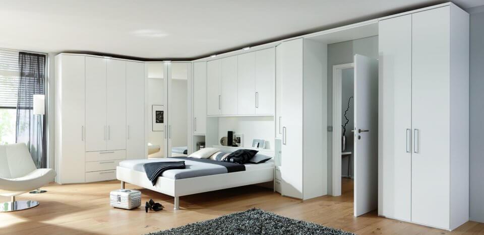 большой угловой белый шкаф в спальне