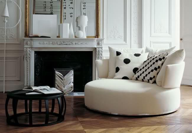 Круглый диван в интерьере гостиной с камином
