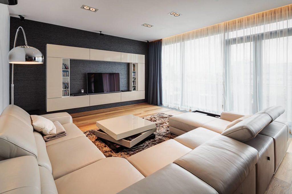 Модульный угловой диван в гостиной перед телевизором